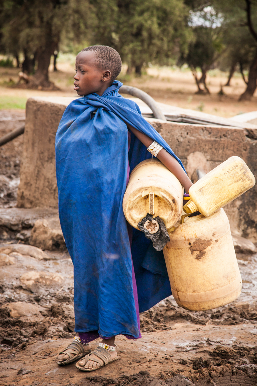 Photo of girl holding water containers