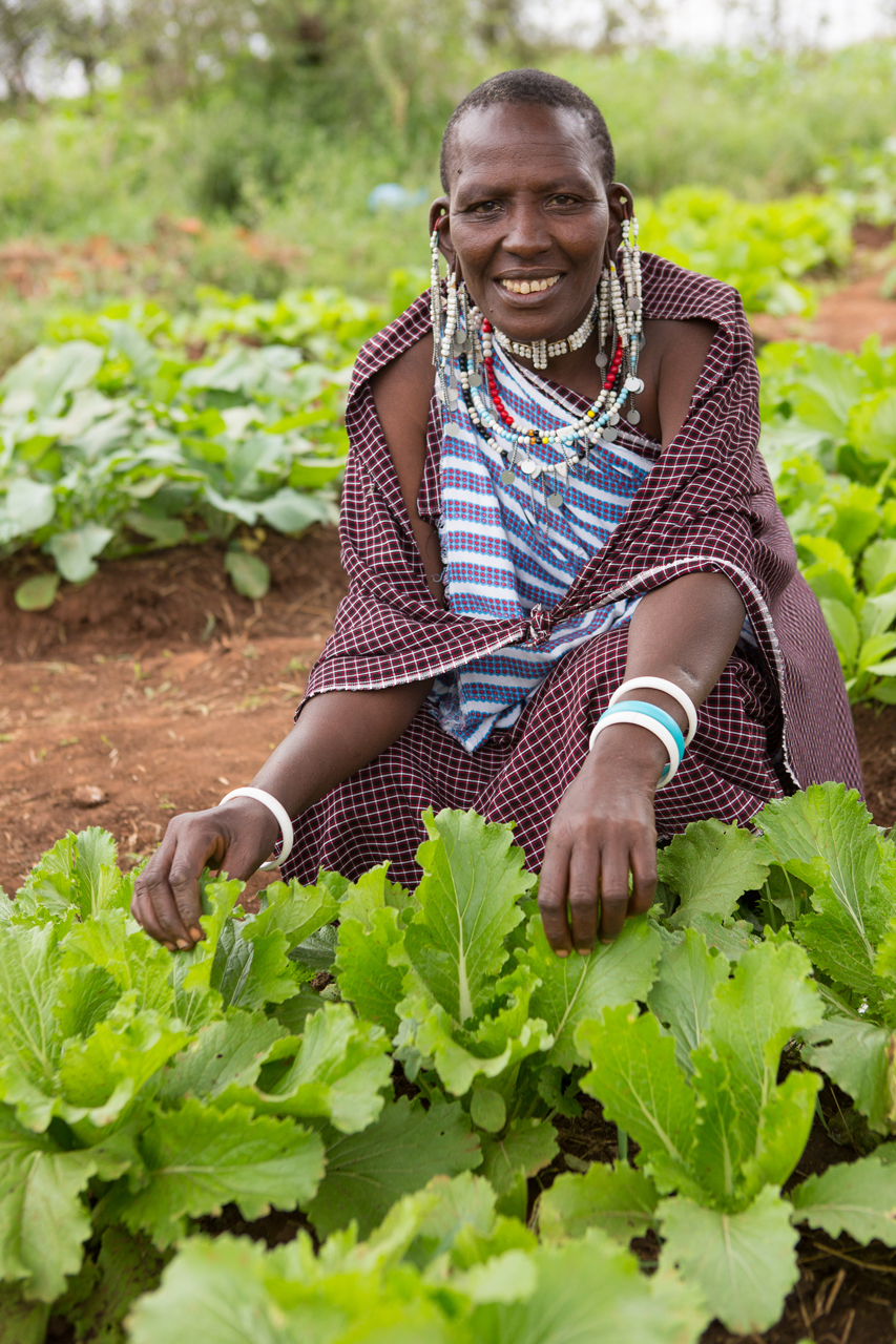 Photo of lady squatting over vegetable garden