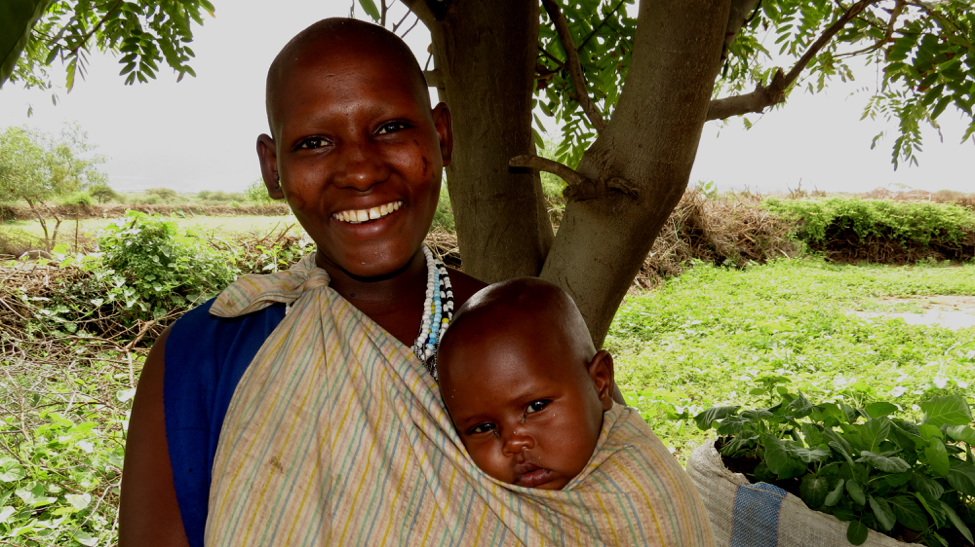 Nosim and her child pictured in front of one of her sack gardens.